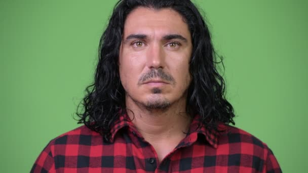 Handsome hipster man against green background