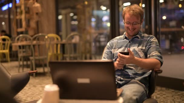 Handsome businessman smiling while using phone in the cafe at night