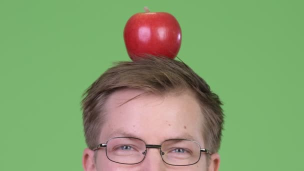 Portrait Of Young Man Doctor Holding Red Apple On His Head