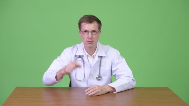 Portrait Of Young Man Doctor Sitting While Pointing Finger Up