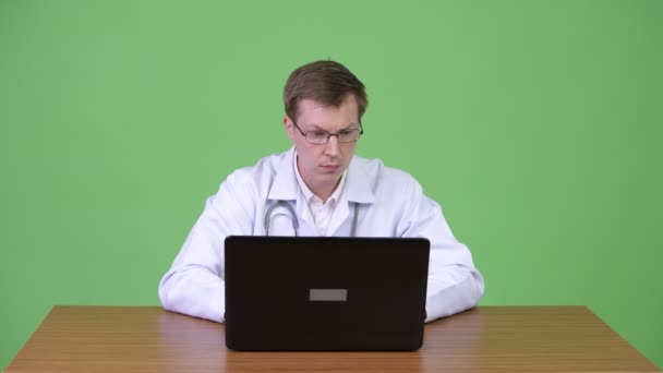 Portrait Of Young Man Doctor Sitting And Using Laptop Computer