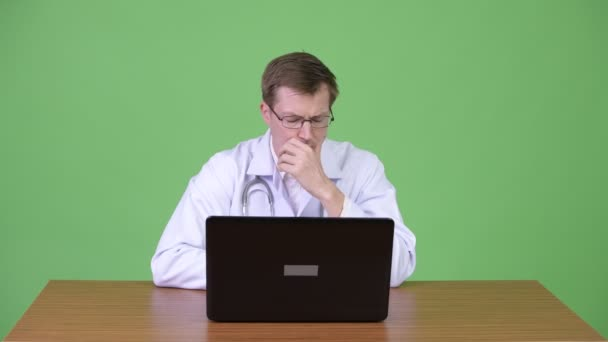 Portrait Of Young Man Doctor Sitting And Using Laptop Computer While Thinking