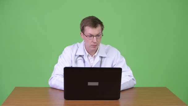 Man Doctor Sitting And Using Laptop Computer While Talking And Greeting Patient