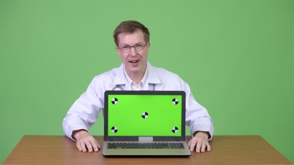Doctor Sitting And Showing Green Screen Laptop Computer While Talking