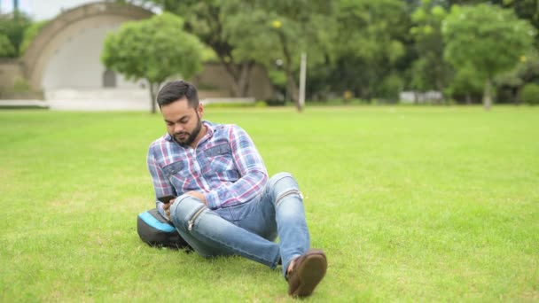 Handsome Indian Man In Park Lying Down On Grass And Using Mobile Phone