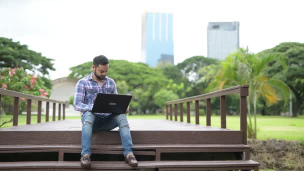 Young Handsome Indian Man In Park Using Laptop Computer