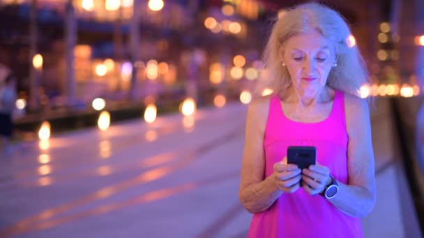 Portrait Of Senior Woman Outdoors At Night Using Mobile Phone