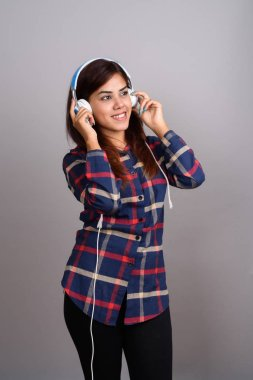 Young beautiful Indian woman listening to music against gray bac