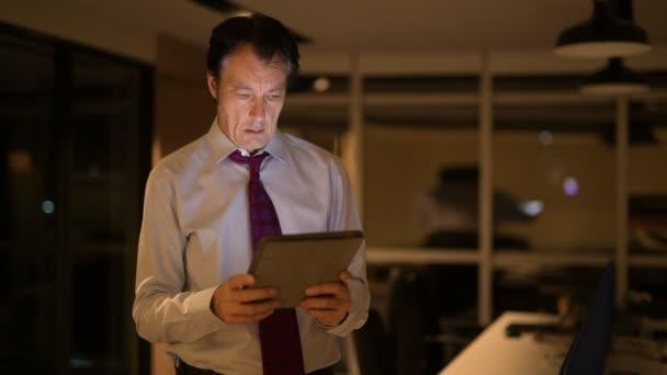 Starší podnikatel v úřadu v noci pomocí digitálních tabletový počítač