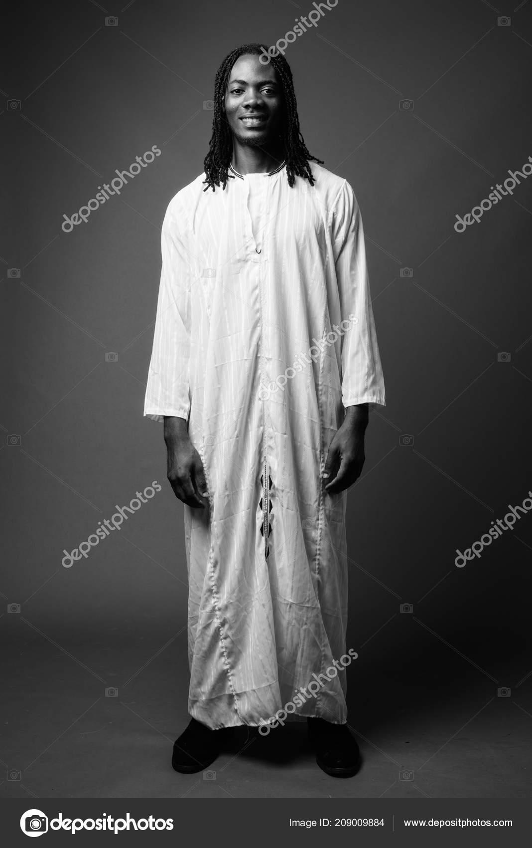e621ba7b1b69 Giovane uomo africano bello indossando abiti tradizionali in nero– immagine  stock