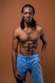 Junge stattliche afrikanische Mann ohne Hemd vor braunem Hintergrund