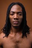 junger gutaussehender afrikanischer Mann ohne Hemd vor braunem Hintergrund