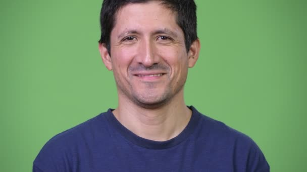 Happy Hispanic man smiling against green background