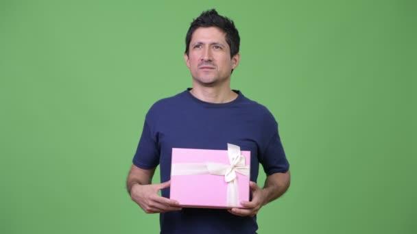Šťastný muž hispánského původu myšlení podržíte-dárková krabička