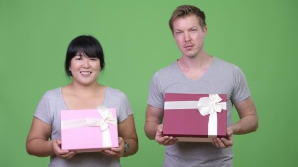 Studio záběr nadváhu Asijské žena a mladík skandinávské společně proti chroma klíč se zeleným pozadím