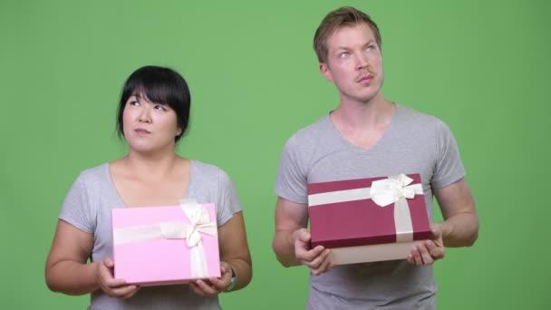 Mladý pár šťastný multietnické drží krabičky a myšlení společně