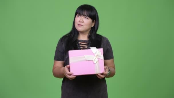 Happy nadváhu asijských žena myslí podržíte krabičky