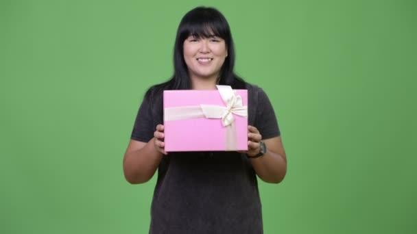 Šťastná nadváhu Asijské žena dává krabičky