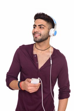 Studio shot of young happy Indian man listening to music while h