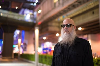 Mature bald bearded tourist man exploring the city streets at night