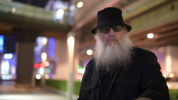 Mature bearded tourist man thinking in the city streets at night