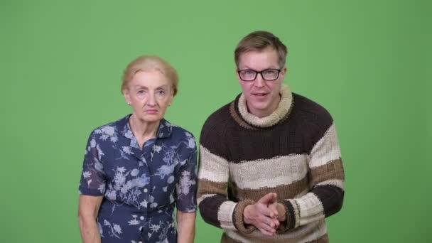 Vnuk slaví zatímco babička hledá naštvaná, zelené pozadí