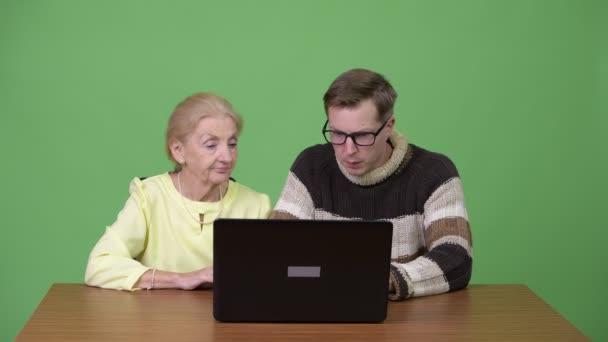 Senior geschäftsfrau und schönen jungen Mann mit Laptop zusammen