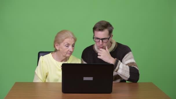 Senior geschäftsfrau und schönen jungen Mann mit Laptop und immer gute Nachricht zusammen