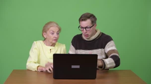 Senior geschäftsfrau und schönen jungen Mann mit Laptop und Panik zusammen