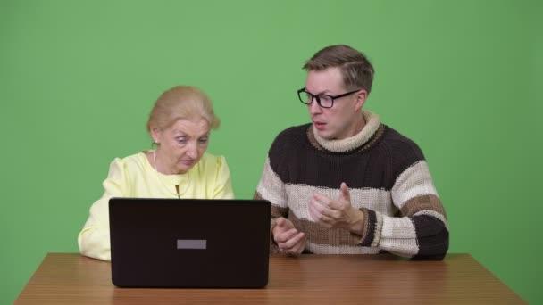 Junger Mann lehrt senior geschäftsfrau wie man Laptop und müde