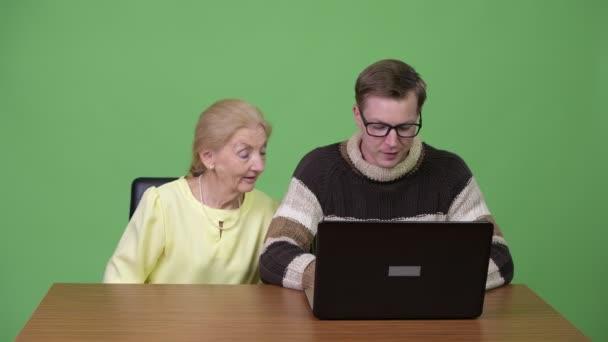 Glücklich senior geschäftsfrau und schönen jungen Mann mit Laptop zusammen