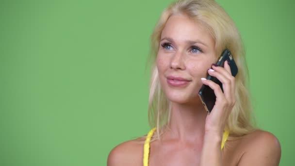 Fiatal boldog szép szőke nő beszél a telefonon