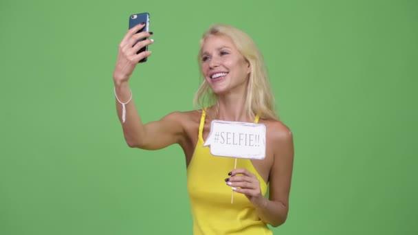 Mladá šťastná krásná blondýnka s selfie znakem papíru