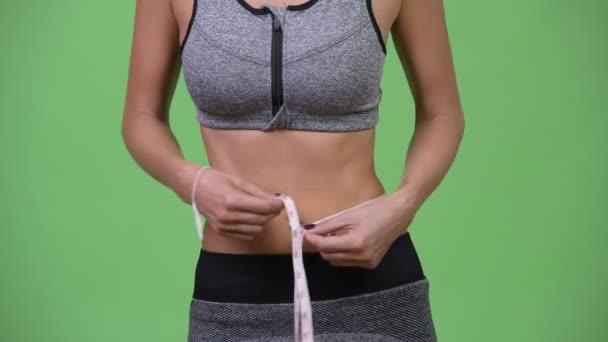 Mladá žena měřící její uchycení a zdravé tělo