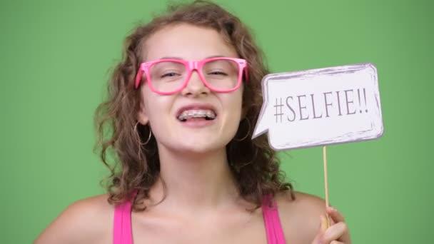 junge glückliche schöne Nerd-Frau mit Selfie-Papierschild