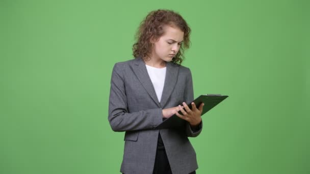 Young happy beautiful businesswoman thinking while reading on clipboard