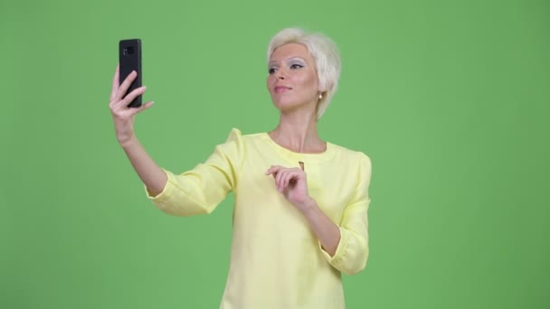 Happy beautiful businesswoman with short blond hair taking selfie