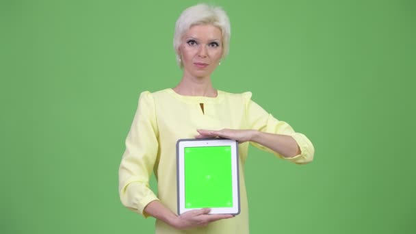 Happy beautiful businesswoman with short blond hair showing digital tablet