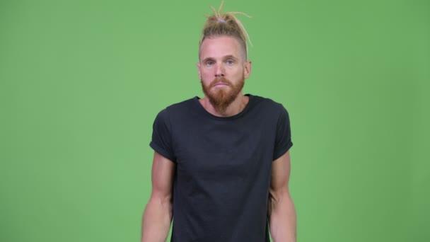 Handsome bearded man with dreadlocks shrugging shoulders