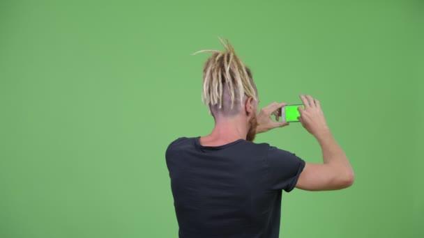 Rückansicht eines bärtigen Mannes mit Dreadlocks beim Fotografieren mit dem Handy