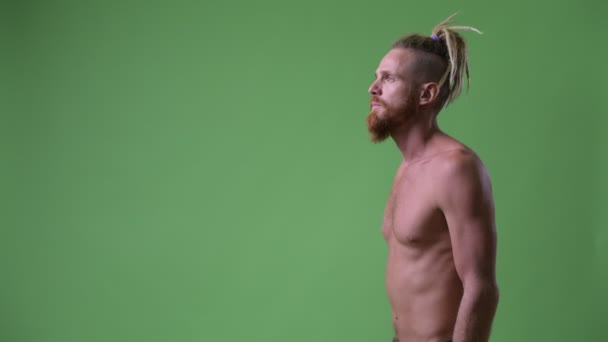 Profile view of handsome muscular bearded man with dreadlocks shirtless