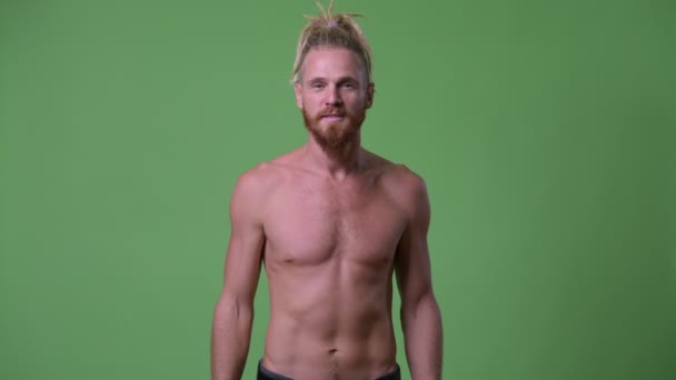 Happy handsome muscular bearded man with dreadlocks pointing up shirtless