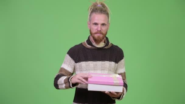 Vousatý muž s úsměvem při otevírání krabičky