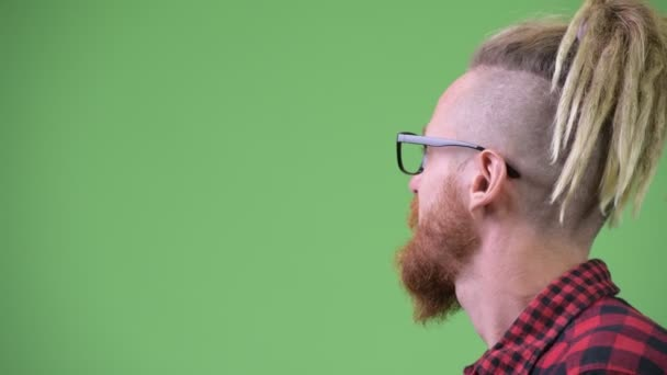 Profile view of happy handsome bearded hipster man with dreadlocks
