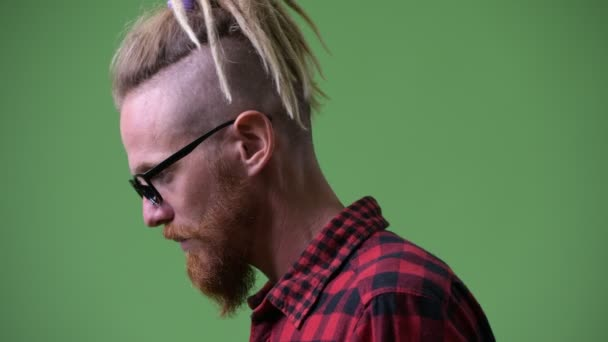 Profile view of handsome bearded hipster man with dreadlocks looking up