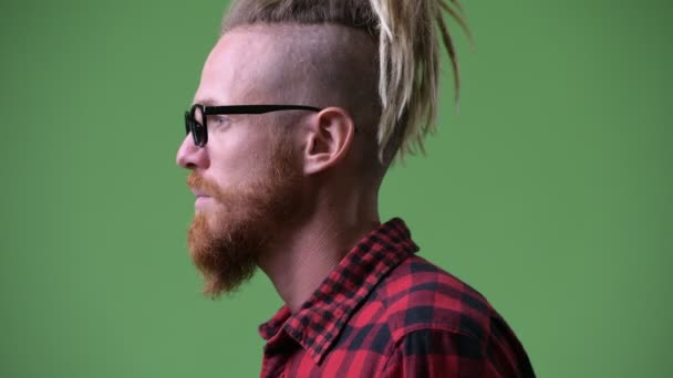 Profile view of handsome bearded hipster man with dreadlocks looking to camera