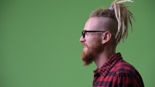 Profile view of happy handsome bearded hipster man with dreadlocks laughing