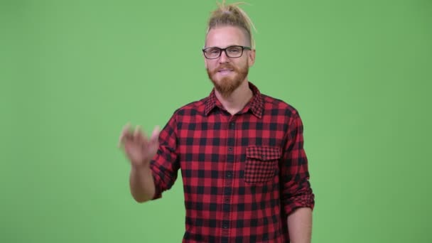 Studio shot of handsome bearded hipster man with dreadlocks against chroma key with green background