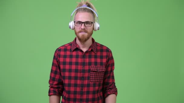 Handsome bearded hipster man with dreadlocks listening to music