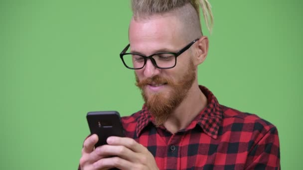 Happy handsome bearded hipster man with dreadlocks smiling while using phone
